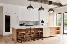 04 The kitchen is done with sleek white cabinets, a marble backsplash and a matching island