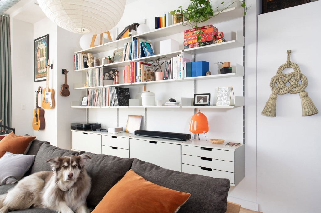 The loft is given much storage space with sleek  plywood cabinets, open shelves and a comfy sofa