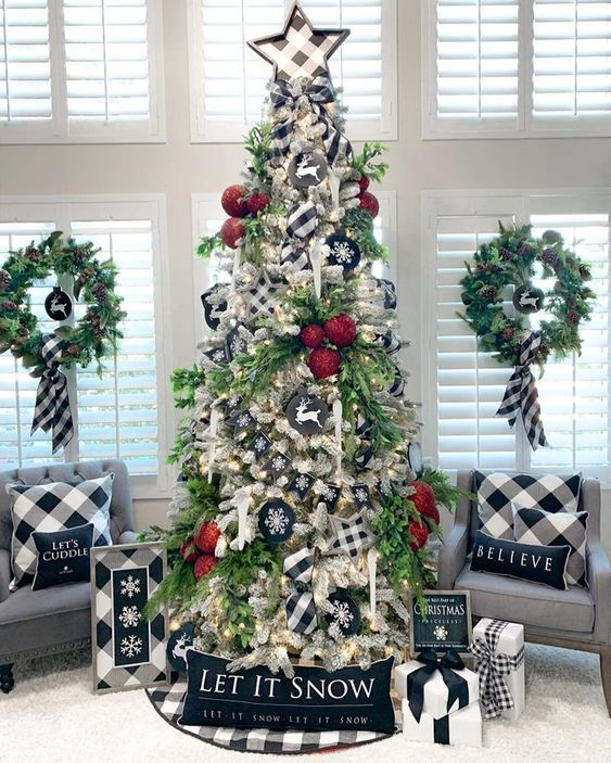 a Christmas tree decorated with buffalo check stars, buffalo check pillows, artworks and ribbons for a stylish vintage look