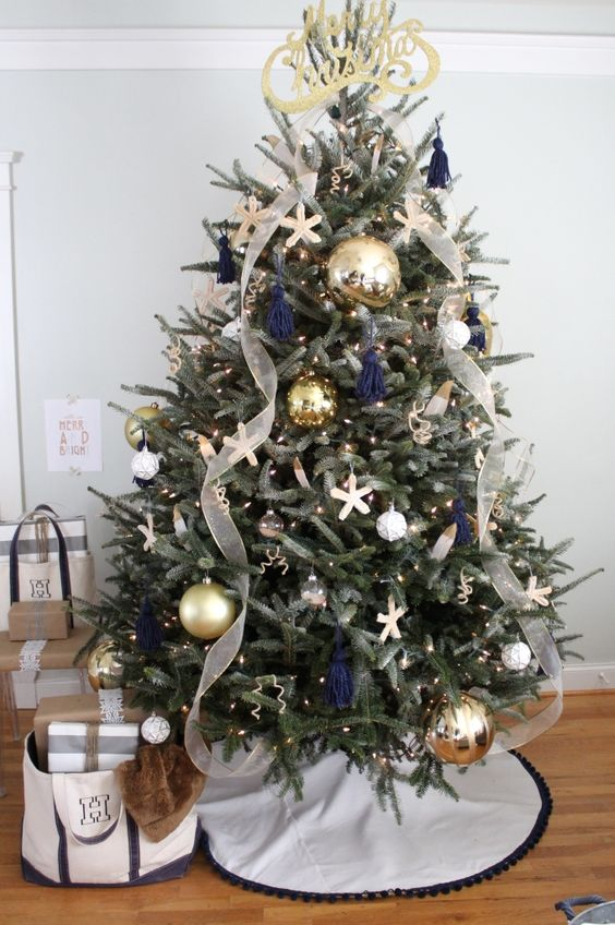 a chic beach Christmas tree with lights, navy tassels, starfish ornaments, oversized metallic ones and ribbons and a calligraphy topper