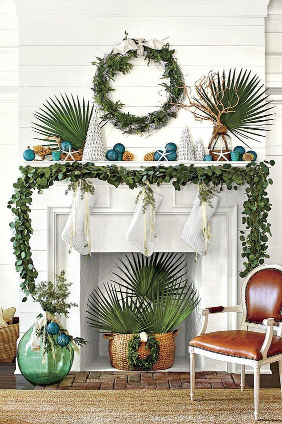 a greenery garland on the mantel, a greenery wreath and tropical leaves for beach Christmas styling