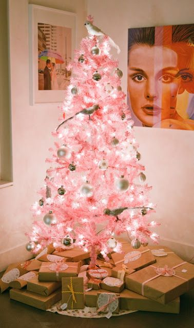 a pastel pink Christmas tree with white and metallic ornaments and quirky birdie ornaments plus lights