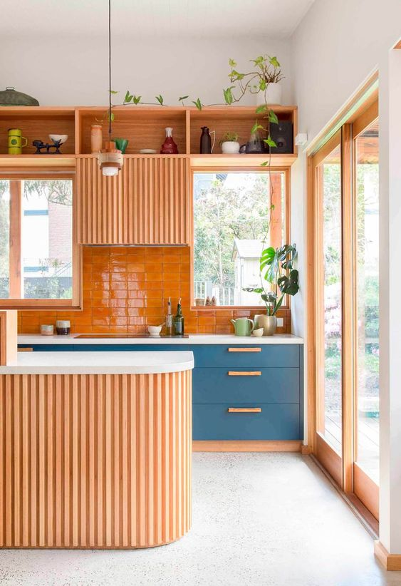 a warm-colored and wood slab clad kitchen with some classic blue cabinets with wooden handles