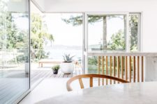 05 Glazed walls and doors allow amazing views and the terrace is decorated in a minimal way, with just a couple of furniture pieces
