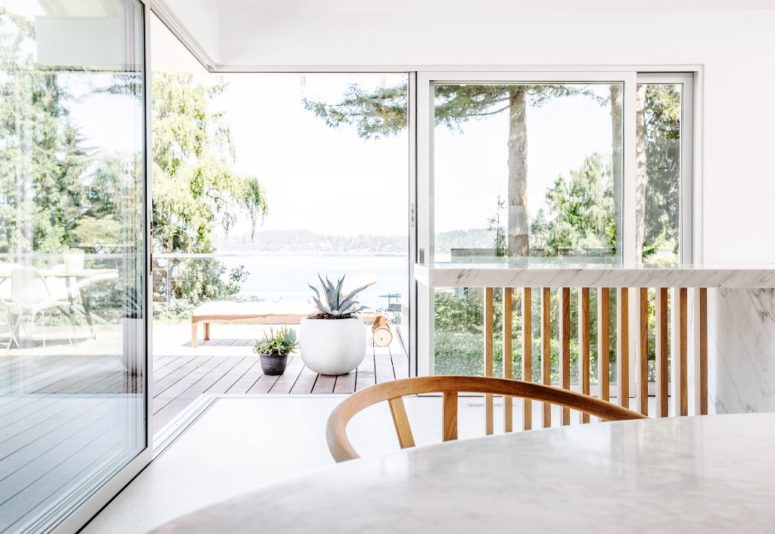 Glazed walls and doors allow amazing views and the terrace is decorated in a minimal way, with just a couple of furniture pieces