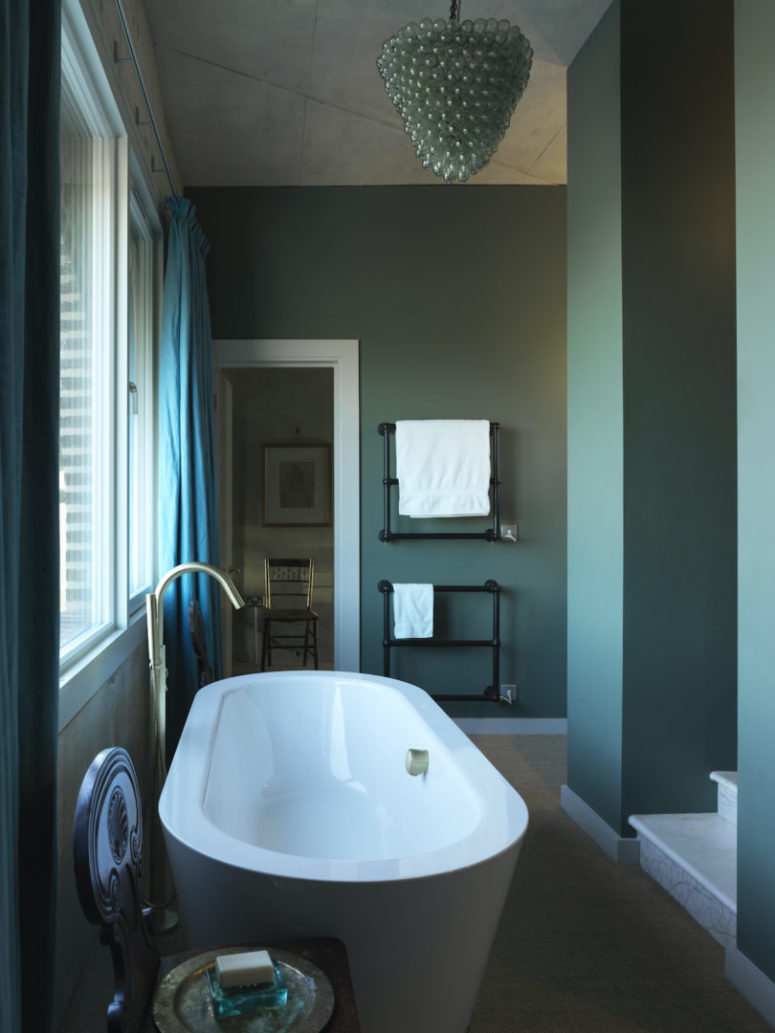 The bathroom is done in blue, with vintage details and a large oval bathtub plus gold touches