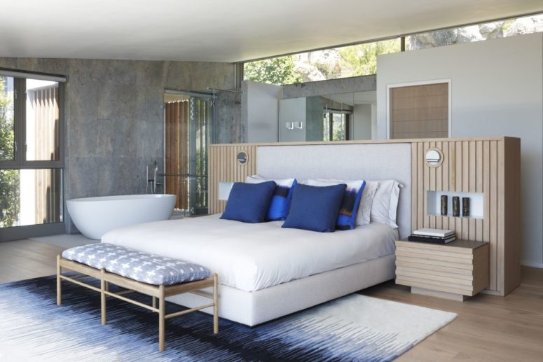 The master bedroom features a bathtub, there's a bright rug and a bed with blue pillows