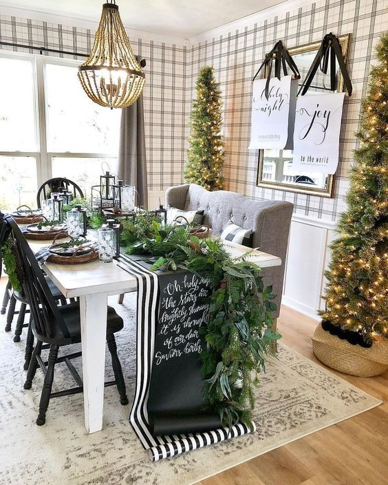 a cozy farmhouse dining space with tall Christmas trees with lights is a chic idea to rock for holidays