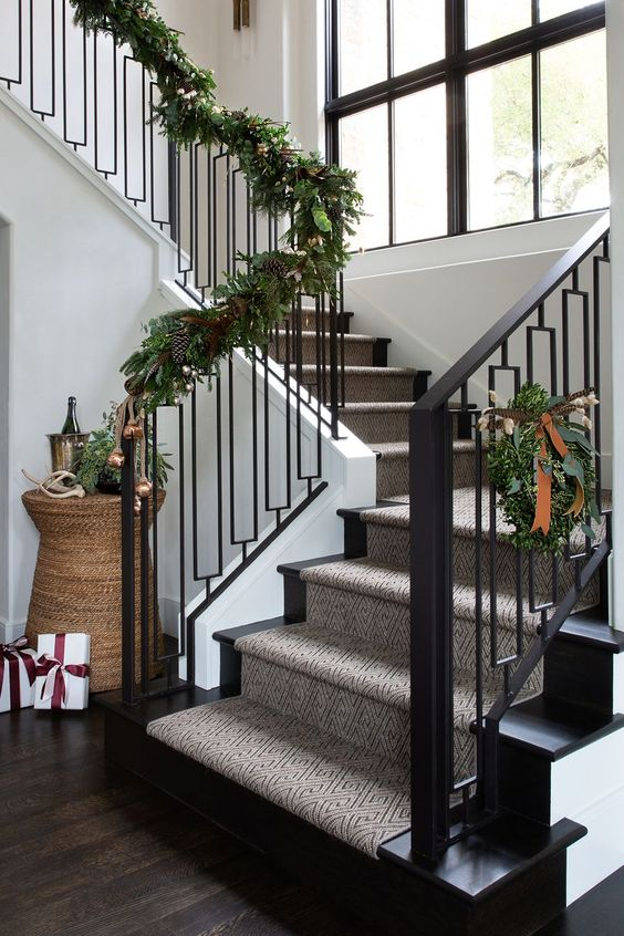 a greenery garland with pinecones covering the railing will bring a festive spirit to the space