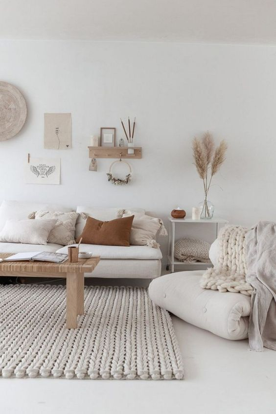 a neutral boho living room with a chunky rug, wood and woven elements and some muted tones