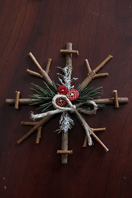 a simple stick snowflake ornament with evergreens, red buttons and twine can be easily DIYed by you or your kids