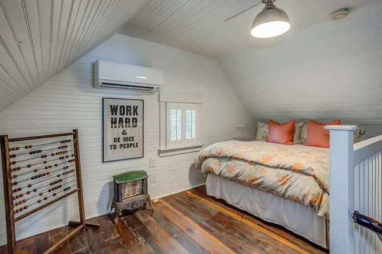 The guest bedroom is a small attic space with a decorative hearth table, a small bed and a little window with shutters