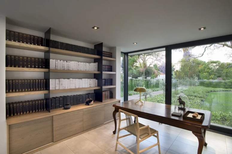 The home office features an elegant desk, large shelves and a sleek storage unit plus a glazed wall