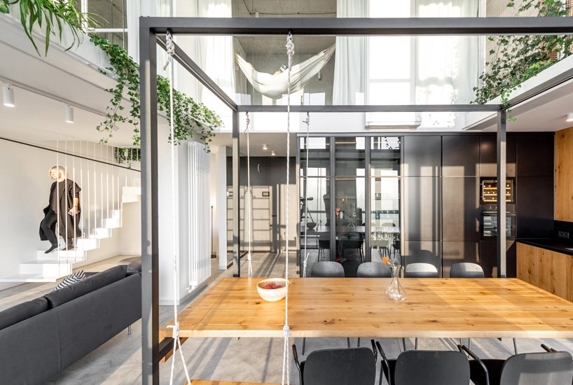 The style of the apartment is contemporary meets minimalist, with black, white, grey and natural wood