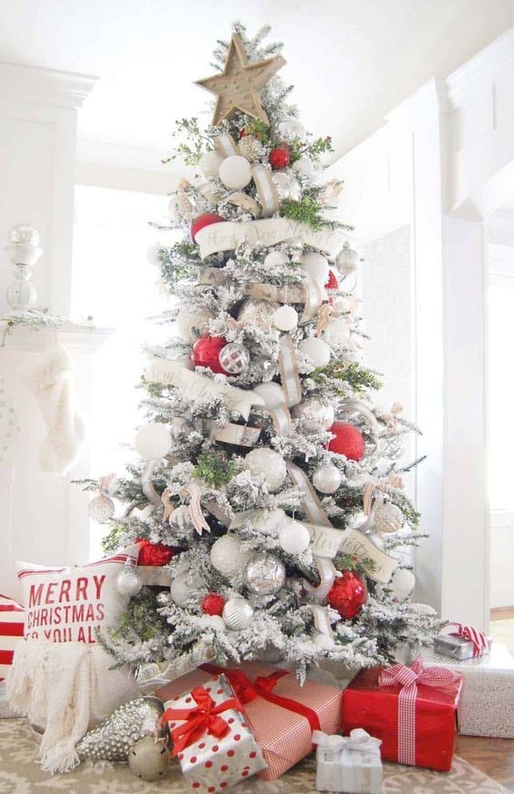 a chic flocked Christmas tree with white and burlap ribbons, white and metallic ornaments and oversized red ones