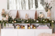 06 a greenery garland with white blooms and berries on the console table to brign a festive spirit to your living room or entryway