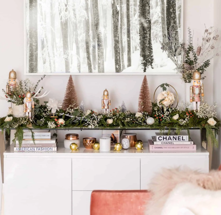 a greenery garland with white blooms and berries on the console table to brign a festive spirit to your living room or entryway