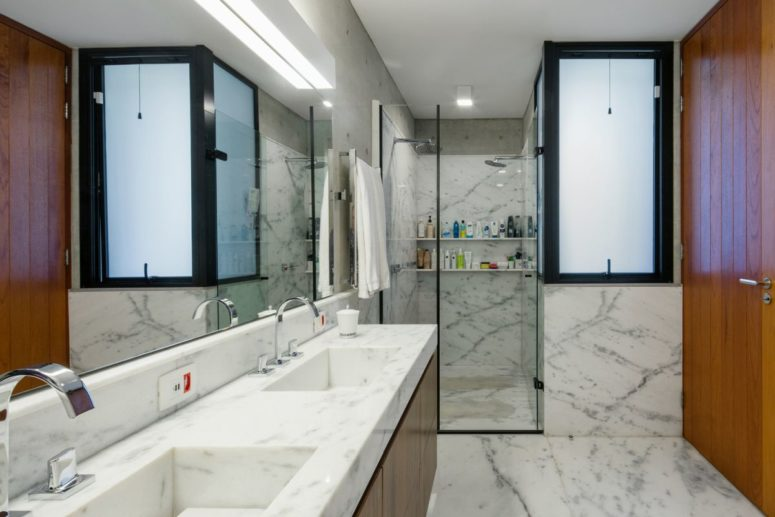 The bathroom is done with white stone and marble and rich-colored wood for a timeless feel and look