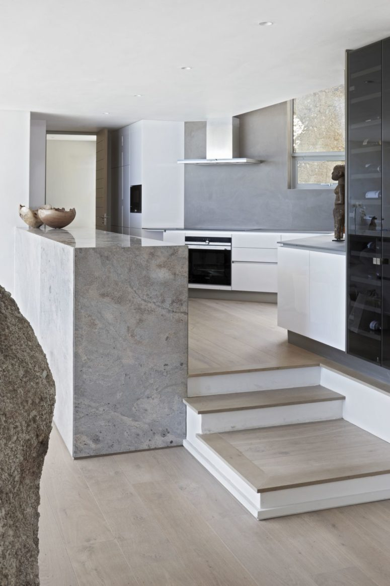 The kitchen is done in white and grey, the kitchen island is done in stone and there are cool views