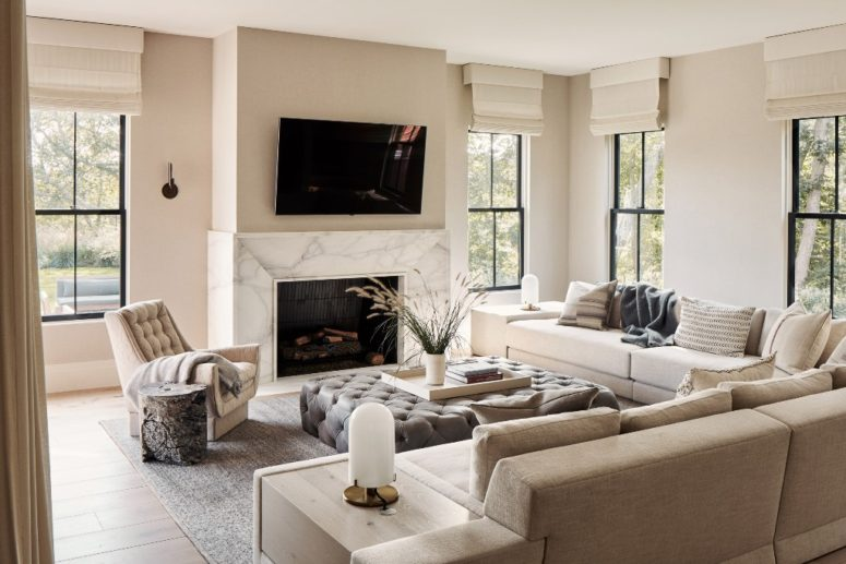 The living room is done with comfy upholstered furniture, a marble clad fireplace and lots of windows