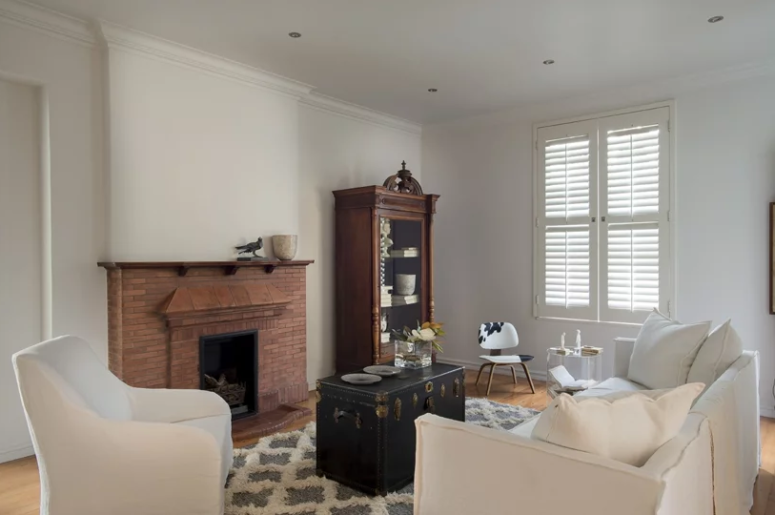 The living room is small and is decorated with vintage furniture, there's a built-in fireplace and a gorgeous chest