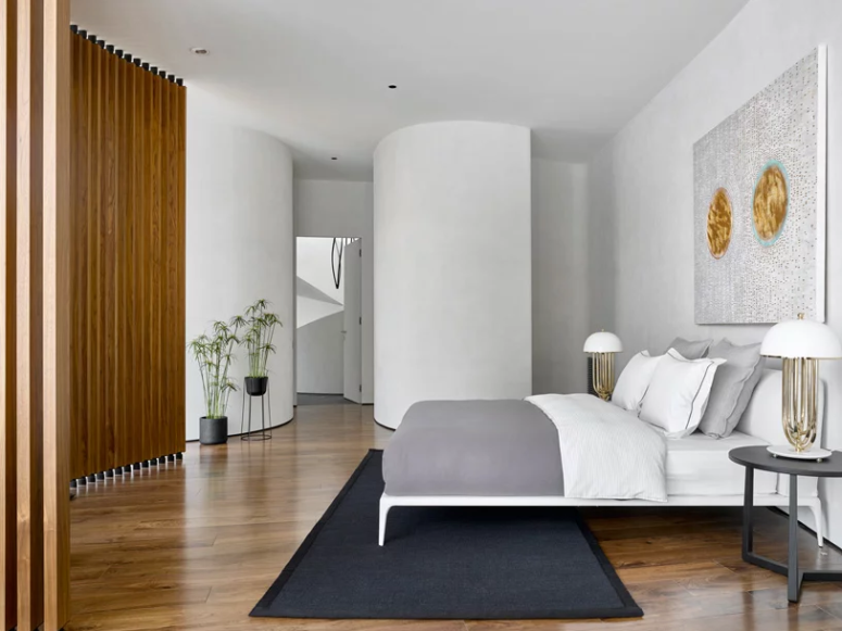 The master bedroom is done with a cool bed, a statement artwork and rugs and looks cozy and private
