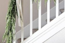 07 a greenery garland with white bows to style your railing in farmhouse style with a touch of vintage