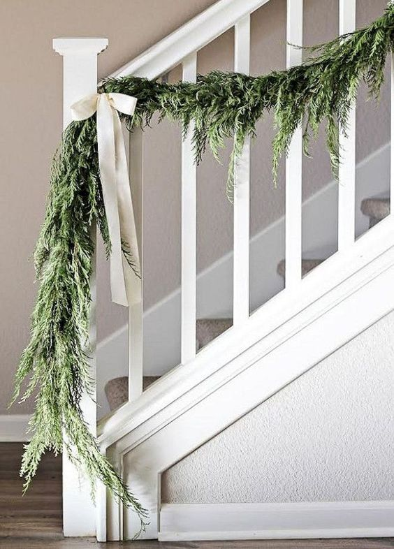 a greenery garland with white bows to style your railing in farmhouse style with a touch of vintage