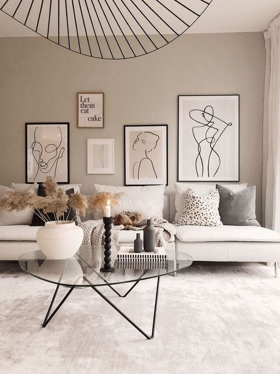 a neutral living room with a gallery wall, touches of black and a neutral sofa plus a glass table on metal legs