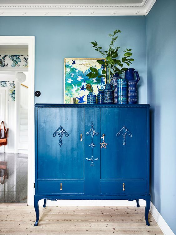 a refined vintage dresser painted classic blue and accented with a star plus blue pottery on top for an edgy touch