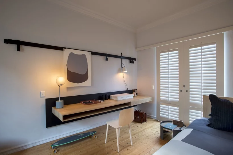 Another bedroom feature a floating desk, lamps, a bed and doors to the garden