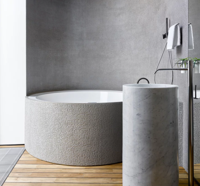 The bathroom features a tile clad round bathtub and a free-standing round sink of white marble