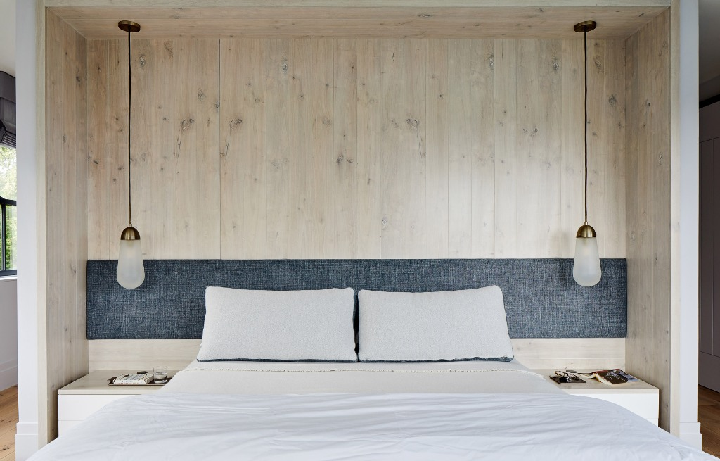 The bedroom features wood, a comfy bed and pendant lamps