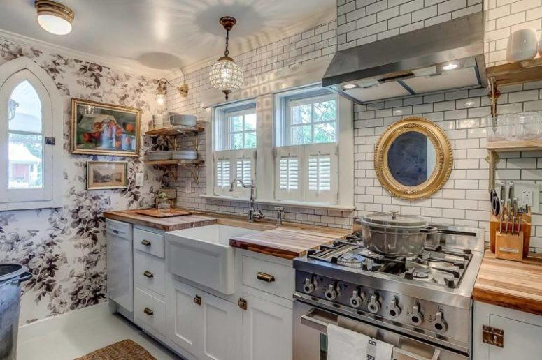 The kitchen features subway tiles, floral wallpaper, farmhouse style cabinets and a crystal pendant lamp