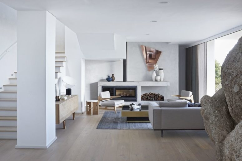 The living room is all-white, with firewood storage, geometric details and super elegant furniture