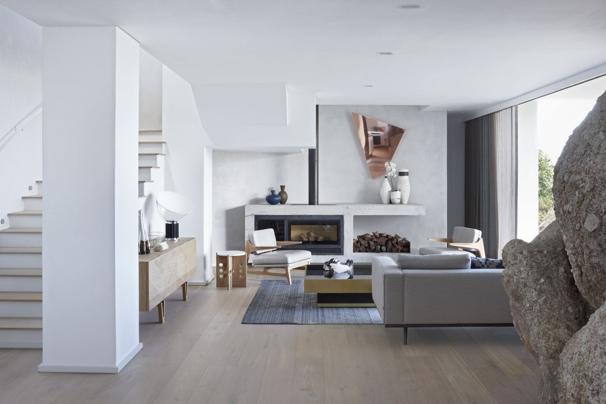The living room is all white, with firewood storage, geometric details and super elegant furniture