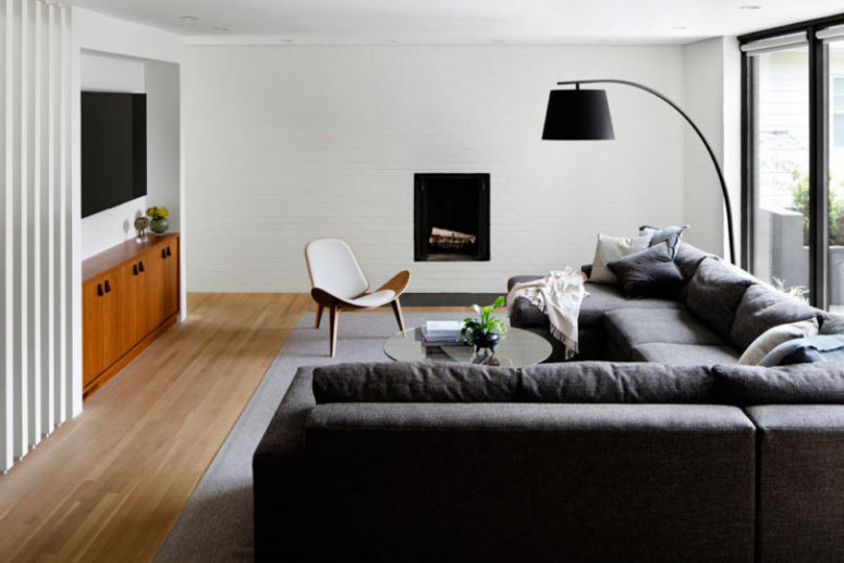 The living room is done with a corner sofa, a TV, a built-in fireplace and md-century modern furniture