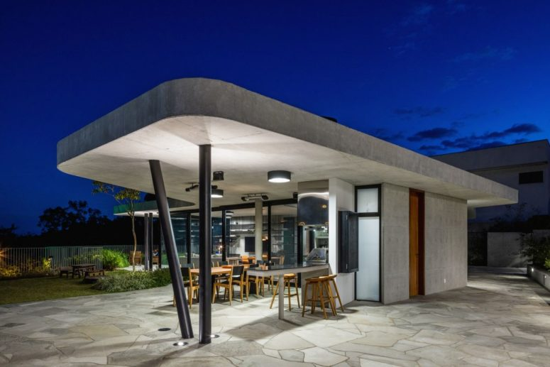 Two slightly angled steel columns support the roof overhang, forming a cozy outdoor terrace