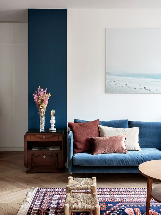 a classic blue sofa and a matching accent wall is a gorgeous idea that will bring a calm and cozy feel to the space