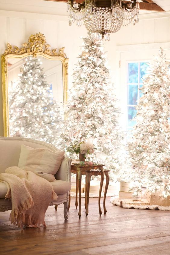 a duo of flocked Christmas trees with lots of lights and neutral and silver ornaments is amazing for a chic space