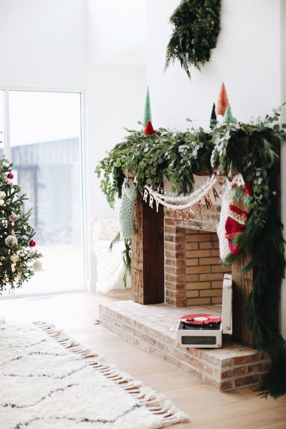 a lush and textural greenery garland on the mantel, white garlands and stockings hanging down from it
