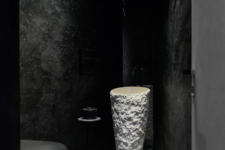 09 There's also a powder room with a black toilet and walls, a sculptural white stone sink and a little table