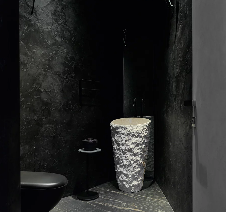 There's also a powder room with a black toilet and walls, a sculptural white stone sink and a little table