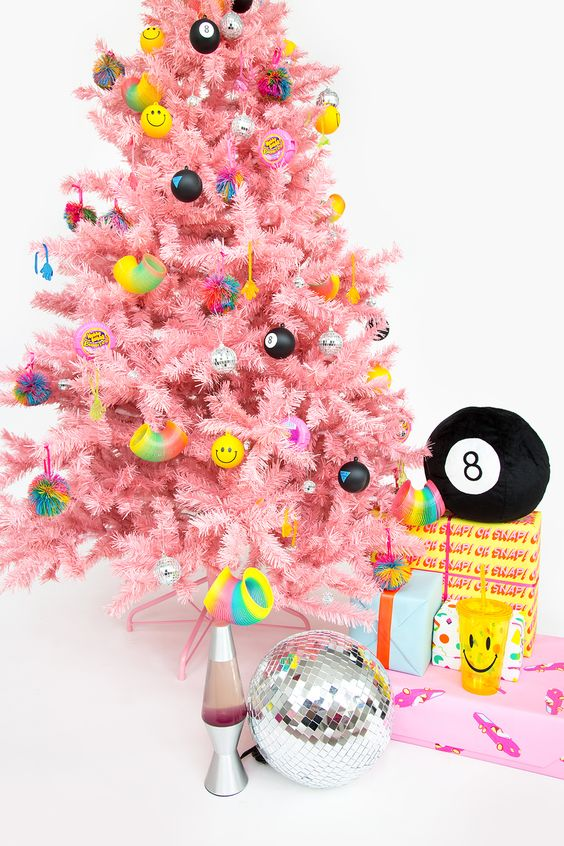 a bright pink Christmas tree with funny and colorful modern ornaments looks fresh and very bold