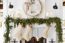 09 a lush evergreen garland on the mantel, chunky knit white stockings for a pretty coastal Christmas space