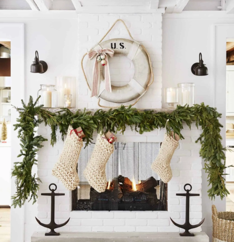 a lush evergreen garland on the mantel, chunky knit white stockings for a pretty coastal Christmas space