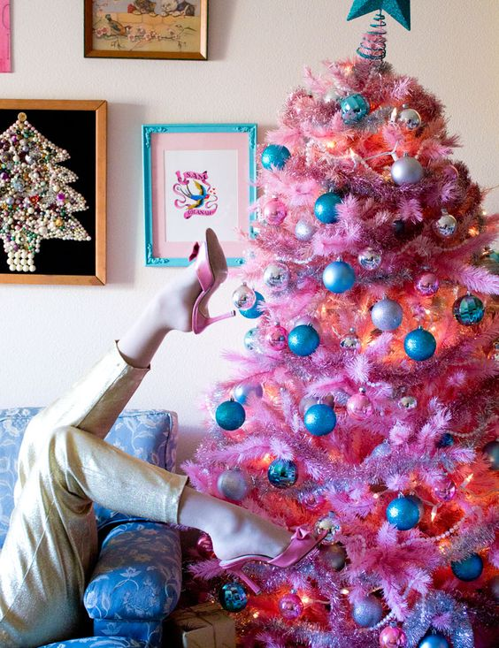 a bright pink Christmas tree with metallic and blue ornaments and lights looks pretty and retro
