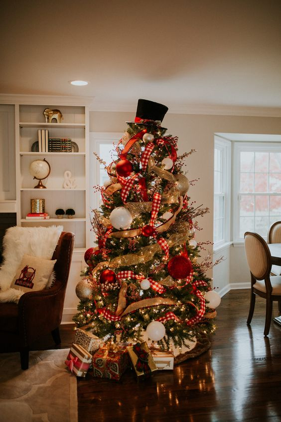 a decorated Christmas tree with lights, burlap and plaid ribbons, oversized red, gold and white ornaments abd a hat on top