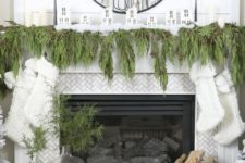 10 a lush evergreen garland on the mantel, mirror and white stockings hanging down from the mantel