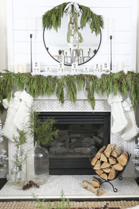 a lush evergreen garland on the mantel, mirror and white stockings hanging down from the mantel